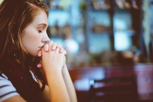 Woman sitting with hands clasped and eyes shut | Anxiety After Child Loss | Grief Counseling | Infant and Pregnancy Loss | Evolve Counseling | Centennial CO 80112
