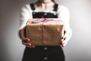 Woman holding Christmas present | Child Loss Grief Counseling | Infant Loss | Pregnancy Loss | Grief During The Holidays | Evolve Counseling Centennial, CO 80112